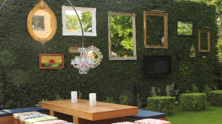 garden mirror ideas showing a series of outdoor mirrors hanging the length of a hedge