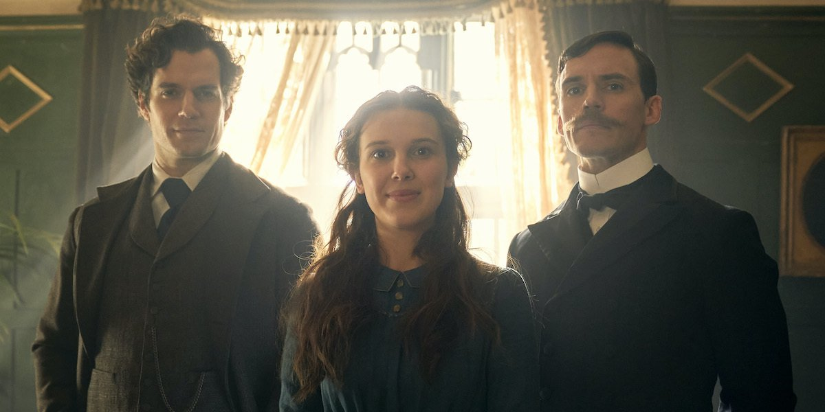 Enola Holmes Henry Cavill Millie Bobbie Brown and Sam Claflin stand together in front of a window