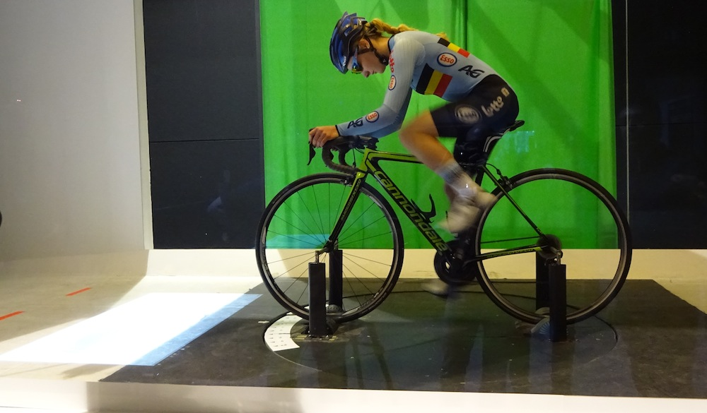 Thumbnail Credit (cyclingweekly.co.uk): tats are projected on the floor in front of the rider