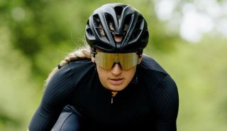 Woman cycles towards the camers whilst wearing SunGod Airas sunglasses
