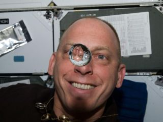 NASA astronaut Clayton Anderson floats on the middeck of space shuttle Discovery during the STS-131 mission in April 2010. In front of him is a water bubble that reflects an upside-down image of the spaceflyer because the light has been refracted.