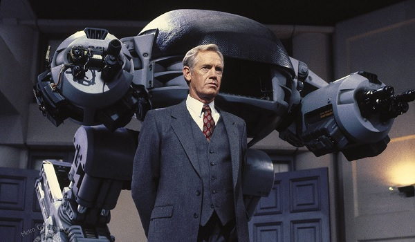 Robocop Dick Jones stands menacingly in front of ED-209