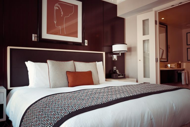 a modern bedroom with a deep red bedroom colour feature wall, white bedding and large print
