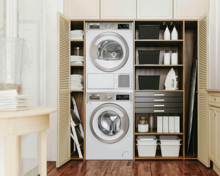 shelving in cream fitted inbuilt cabinets with washsing machine and tumble dryer in a laundry room - smeg