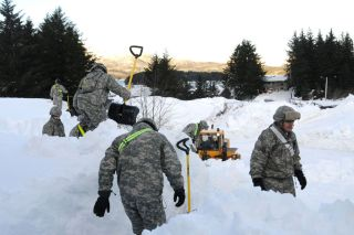 Alaska National Guardsmen clear a building roof in Cordova, near Anchorage, on Jan. 9.
