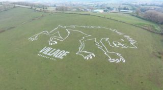 The white outline of a stylised Lycan dominates this Somerset hillside