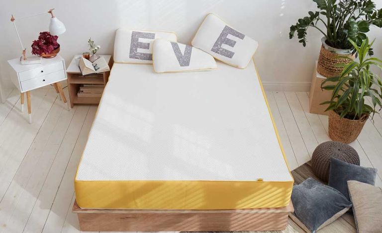 eve mattress review - Eve mattress discount code - Eve mattress on bed with pillows spelling EVE
