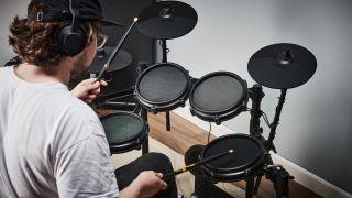 Man plays an Alesis Nitro Mesh drum set