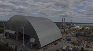 A huge metal arch, called the new confinement shelter, is being slid into place over Chernobyl's destroyed reactor 4.