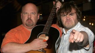 Kyle Gass holding up a guitar and Jack Black pointing at the camera