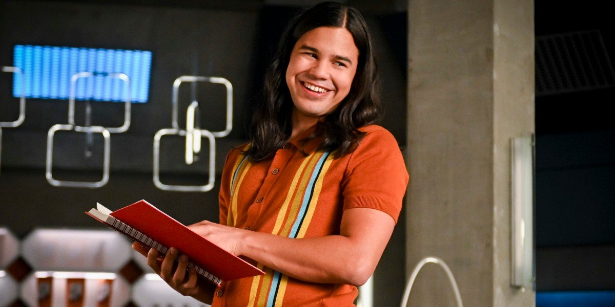Cisco smiling while holding a book The Flash CW