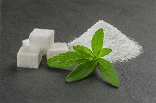 A stevia plant, shown with the sugar substitute made from the leaves.