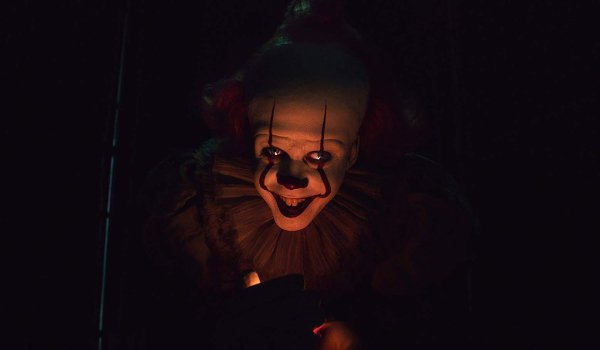 IT Chapter Two Pennywise stands lit by a flame in the darkness