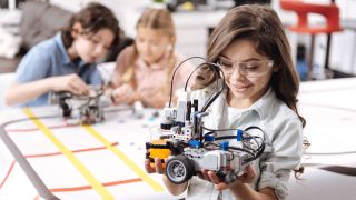 Smiling girl wearing safety goggles holds wheeled robot