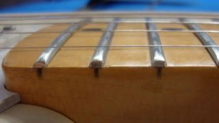 Close-up shot of a guitar fretboard featuring jumbo frets