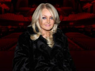 Bonnie Tyler in front of a darkened red theater backdrop