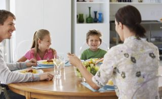 Mother and father sharing a meal with with boy and girl at kitchen table.