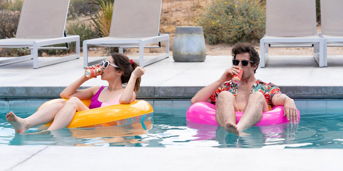 Palm Springs Sandberg and Milioti float in a pool