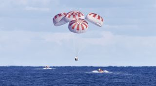 A SpaceX Crew Dragon spacecraft descends under its parachutes at the end of the Demo-1 test flight in March. A test of the parachutes for that spacecraft in April failed when the parachutes didn't open fully.