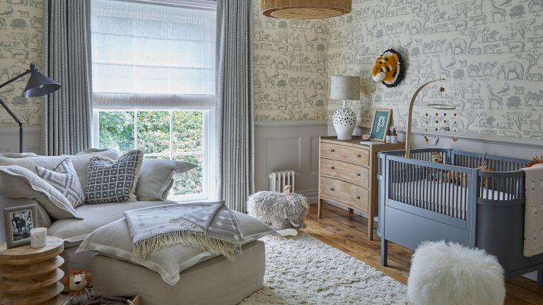 Gender neutral nursery with grey wallpaper and grey nursing chair