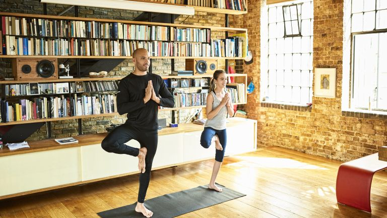 father and daughter do yoga tree pose in loft apartment