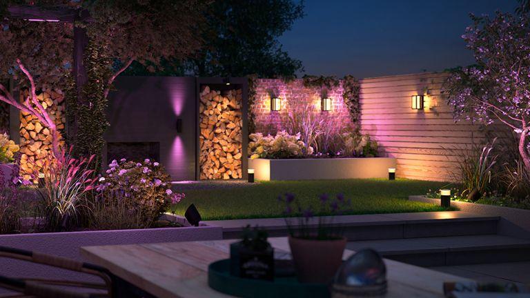 Philips Hue Outdoor lights illuminating a backyard garden