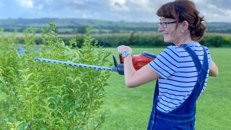 woman trimming a hedge with the Husqvarna 115iHD45 cordless hedge trimmer
