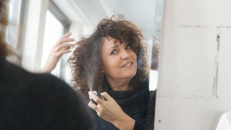 woman spraying hair with dry shampoo