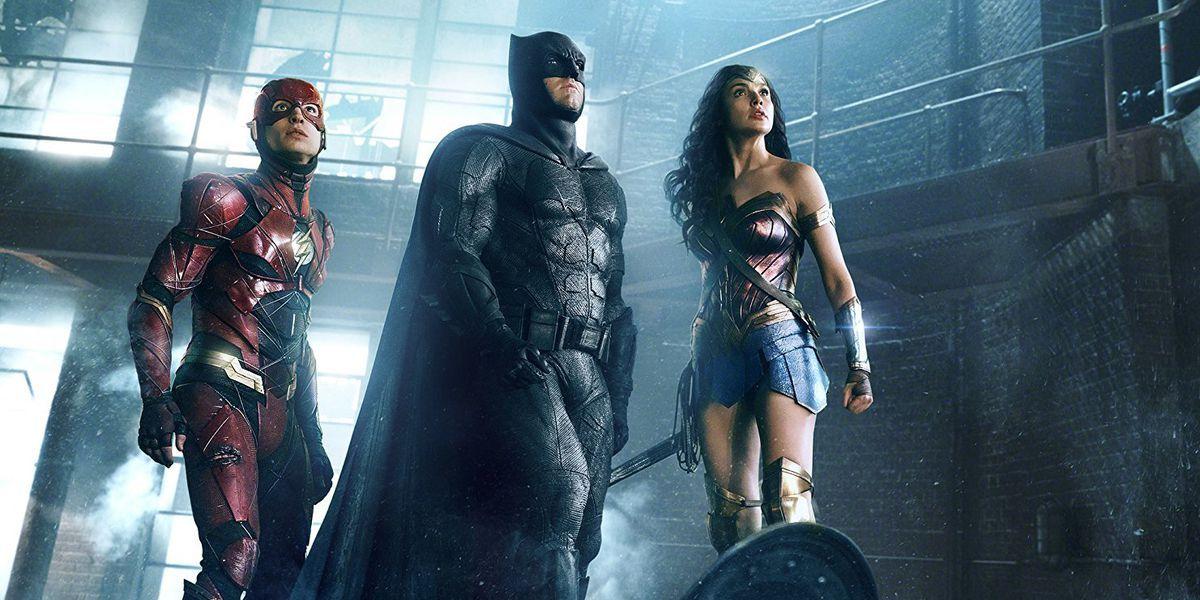 The Flash (Ezra Miller), Batman (Ben Affleck), and Wonder Woman (Gal Gadot) stand in a dark warehous