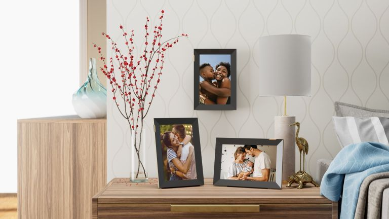 A collection of three Nixplay 10.1-inch Touchscreen Digital Picture Frames on a sideboard