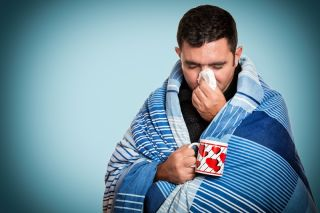 An ill man blowing his nose and holding a cup of tea.