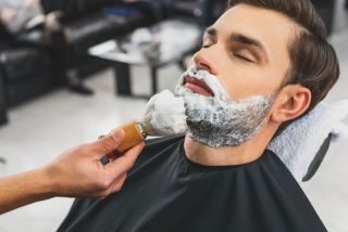 A barber applying shaving cream with a shaving brush to a man's face.