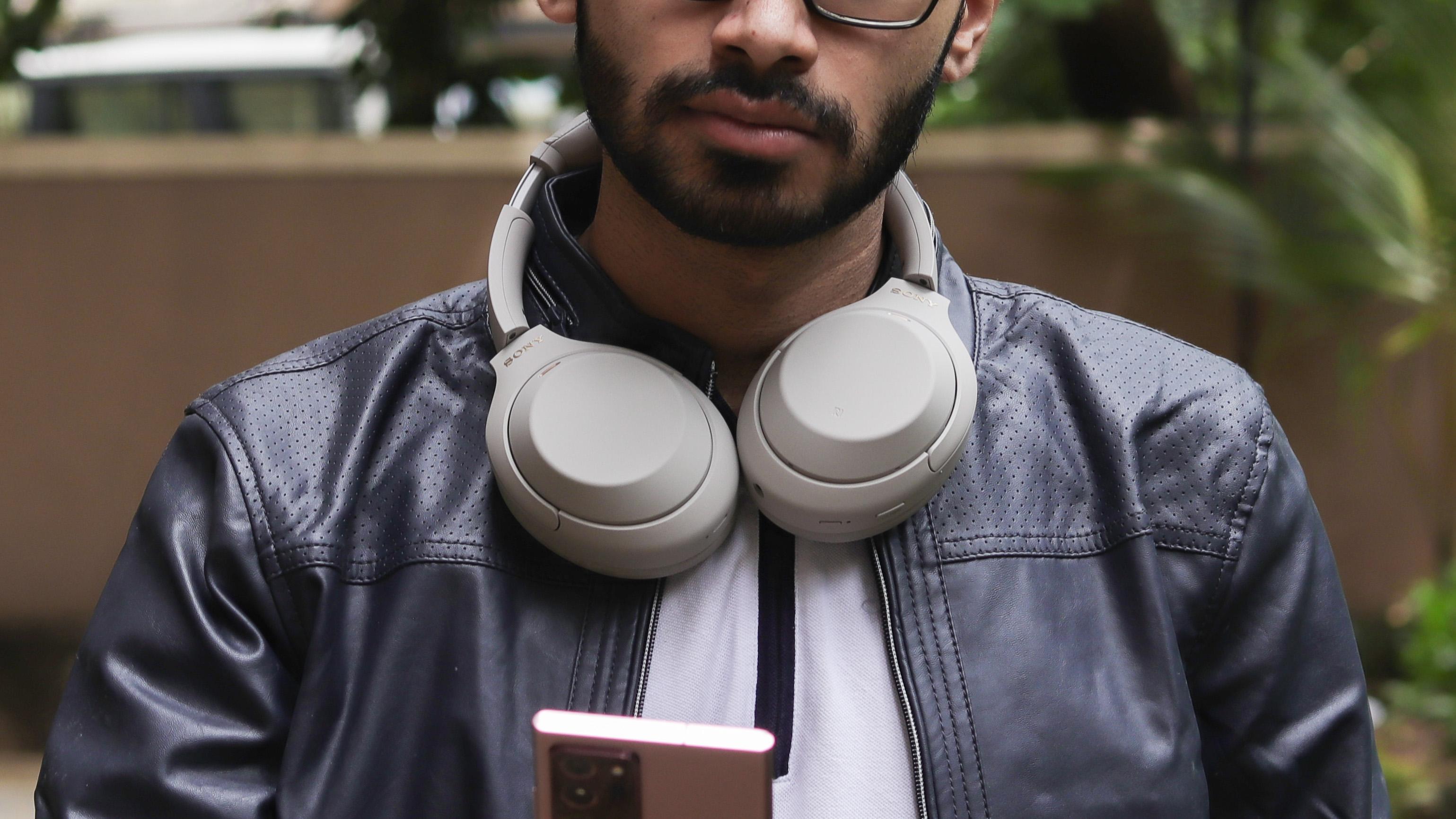 Man wearing Sony WH-1000XM4 headphones around his neck