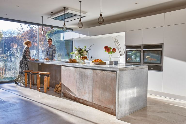 industrial kitchen diner with large metallic island and cage pendant lights