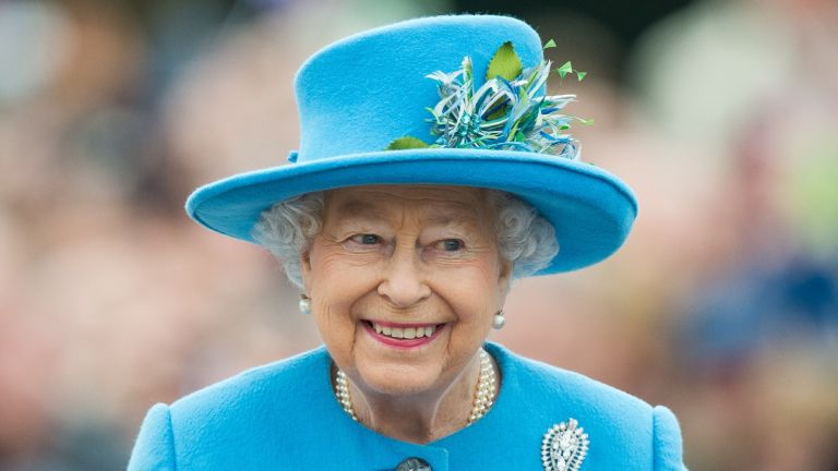 queen smiling in blue hat