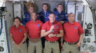 This screenshot shows the welcome ceremony for SpaceX Crew-1 astronauts (bottom, from left) Shannon Walker, Victor Glover, Mike Hopkins and Soichi Noguchi, who arrived at the International Space Station on the night of Nov. 16, 2020. In the back row are NASA astronaut Kate Rubins and cosmonauts Sergey Ryzhikov and Sergey Kud-Sverchkov, who have been living on the orbiting lab since October 2020.