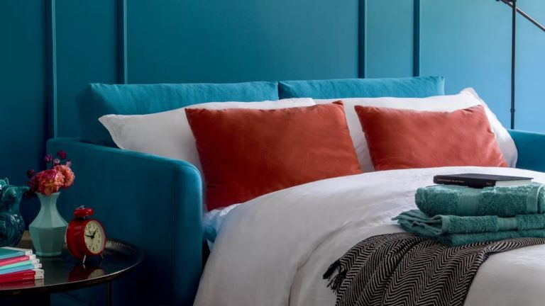 A blue velvet sofa bed with orange cushions and white bedding in a living room with blue panelled walls