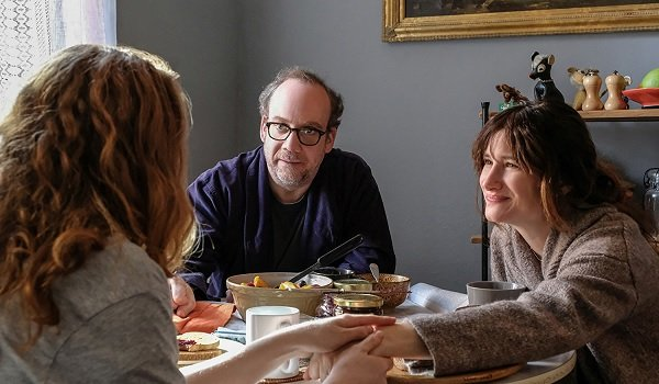 Private Life Paul Giamatti Kathryn Hahn talking at the table with a guest