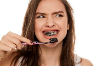 A woman brushing her teeth with activated charcoal toothpaste.