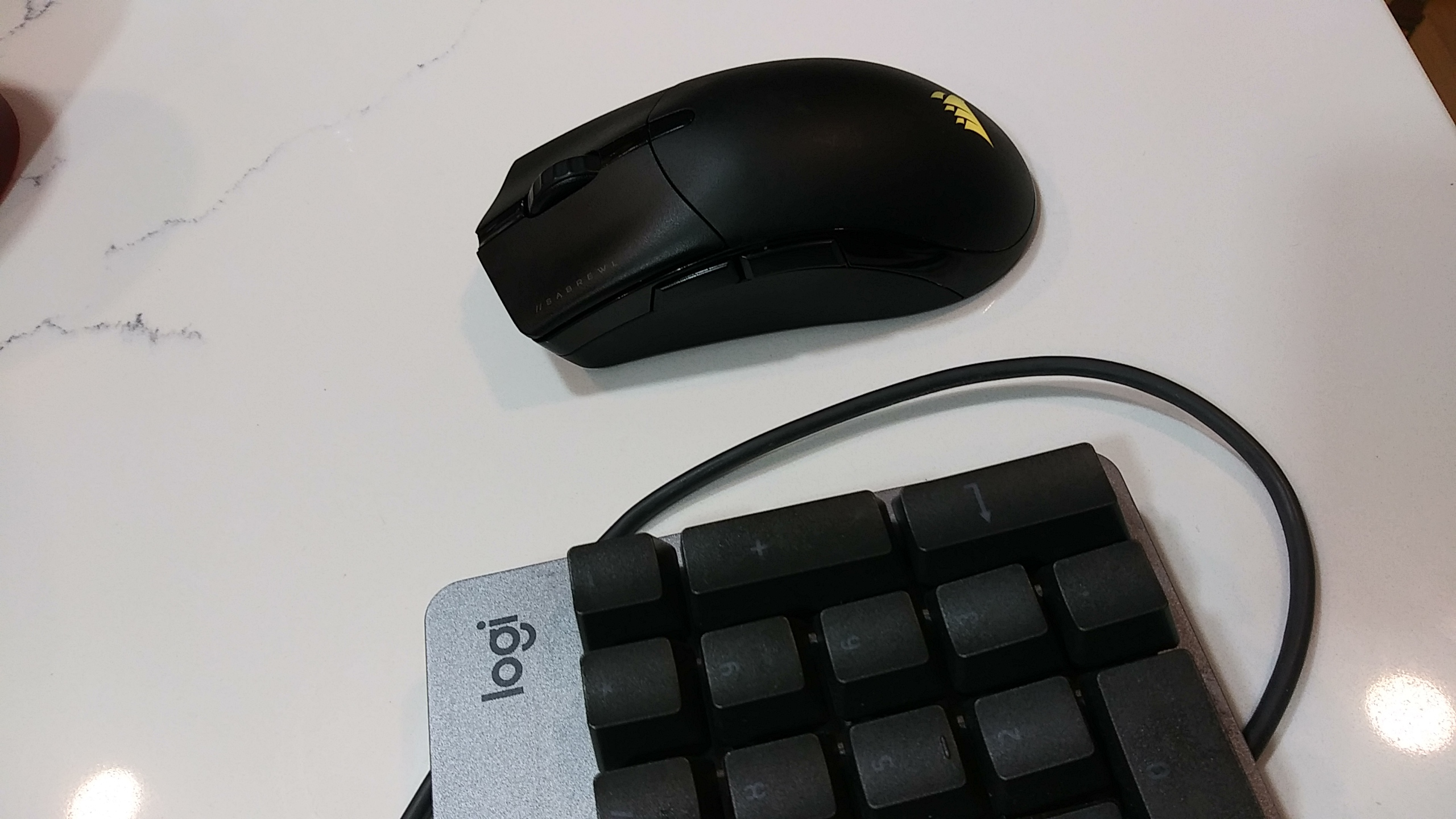 Corsair Sabre RGB Pro on a desk with a glass top next to a keyboard