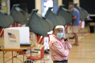 An election clerk in Harris County, Texas, watches over voting booths during early voting for the Texas primary runoffs.