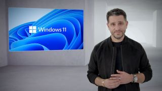 Microsoft's Panos Panay stands in front of the Windows 11 logo