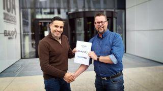 «Ricky Sookermany (Elgiganten, til venstre) og Øyvind Therkelsen (TechRadar) med den signerede aftale i hånden.»