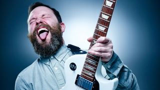 Man playing electric guitar with tongue stuck out