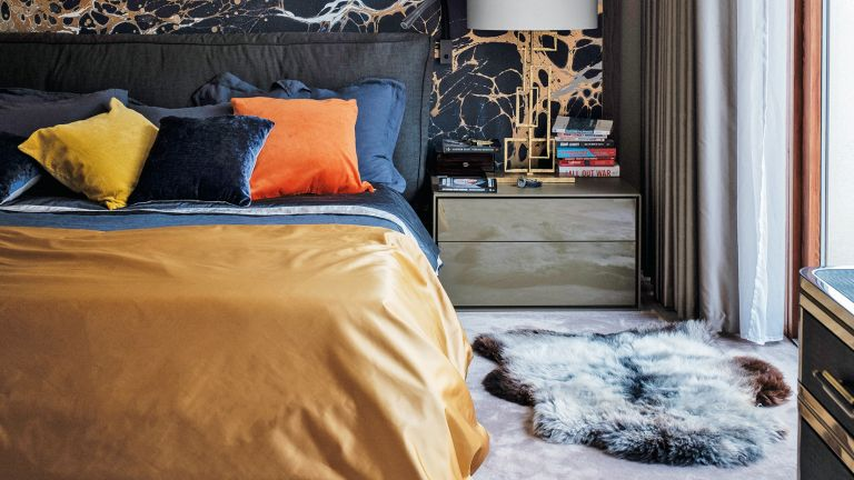 Bedroom with black and orange mural and grey carpet