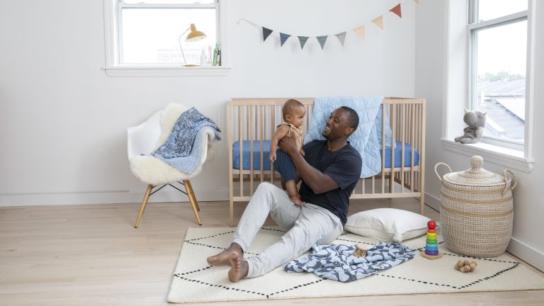 Boys nursery ideas by Brooklinen with cream chair, rug, baby and father