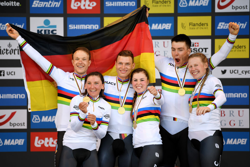 BRUGES BELGIUM SEPTEMBER 22 LR Gold medalists Nikias Arndt of Germany Lisa Brennauer of Germany Tony Martin of Germany Lisa Klein of Germany Max Walscheid of Germany and Mieke Kroger of Germany with world champion jerseys celebrate on the podium while holding the flag of they country during the medal ceremony after the 94th UCI Road World Championships 2021 Team Time Trial Mixed Relay a 445km race from KnokkeHeist to Bruges the day cyclist Tony Martin of Germany withdraws from professional cycling flanders2021 TT on September 22 2021 in Bruges Belgium Photo by Tim de WaeleGetty Images