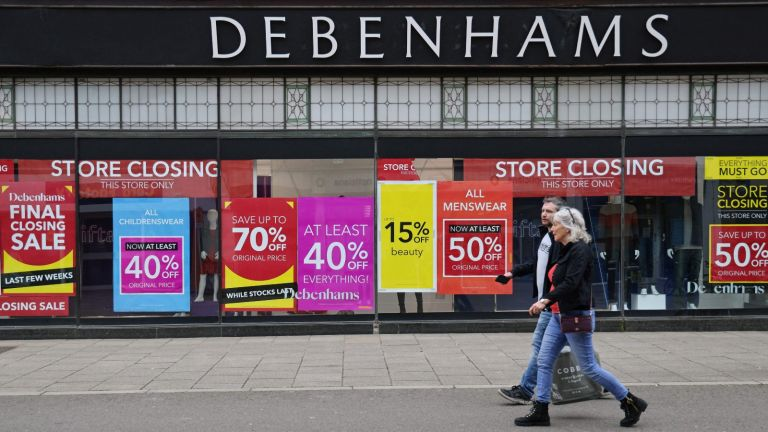 Signs in the window of a closing Debenhams store offer sales bargains on the High Street in Winchester, south west England on March 31, 2021.