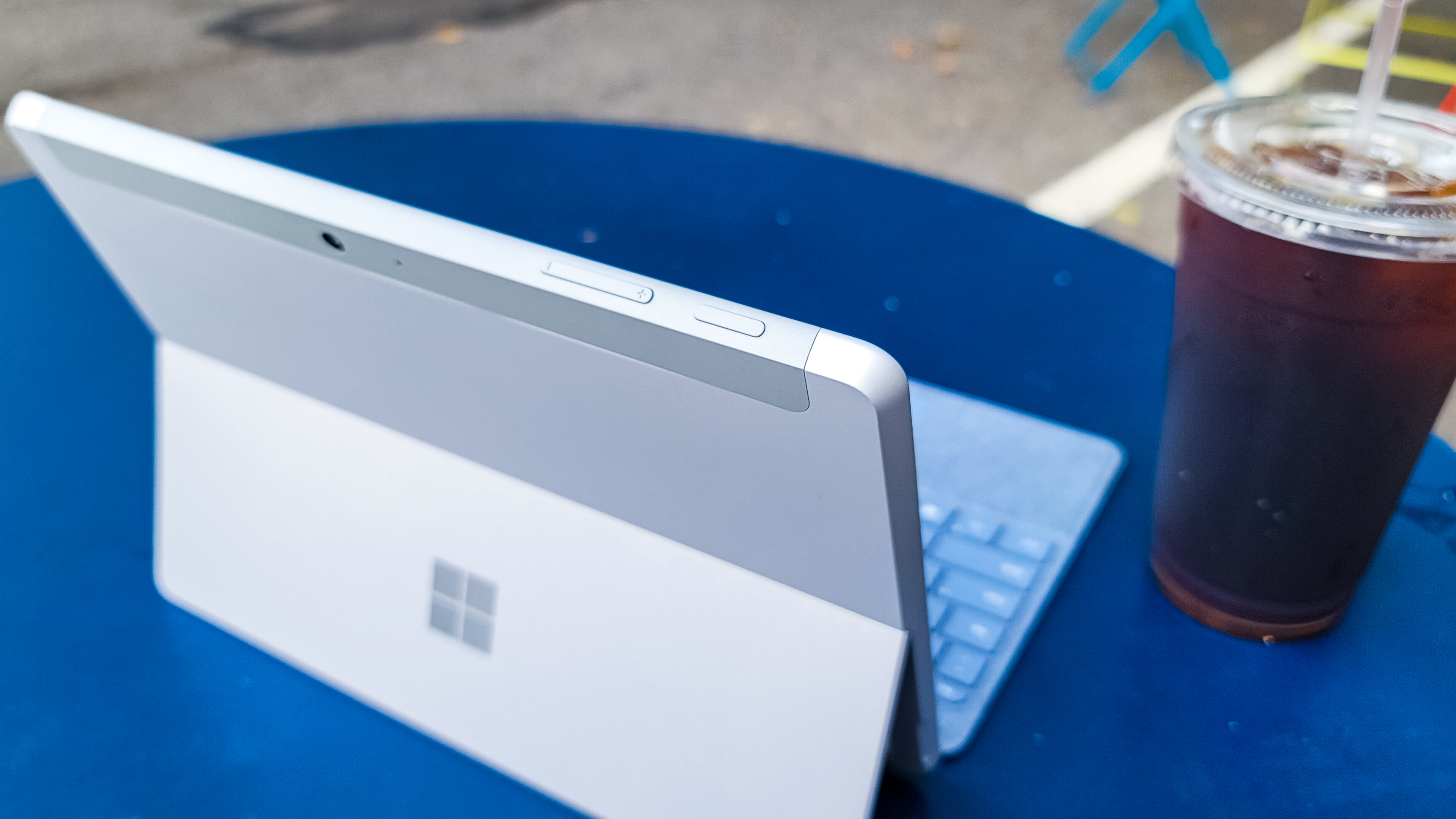 Surface Go 3 on a blue table outdoors next to a cup of iced coffee