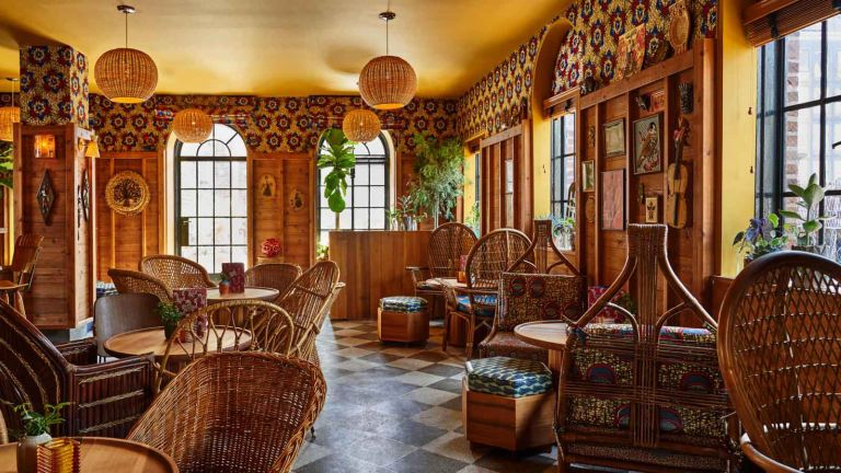 Restaurant at the Freehand Hotel with cane chairs and wall panelling